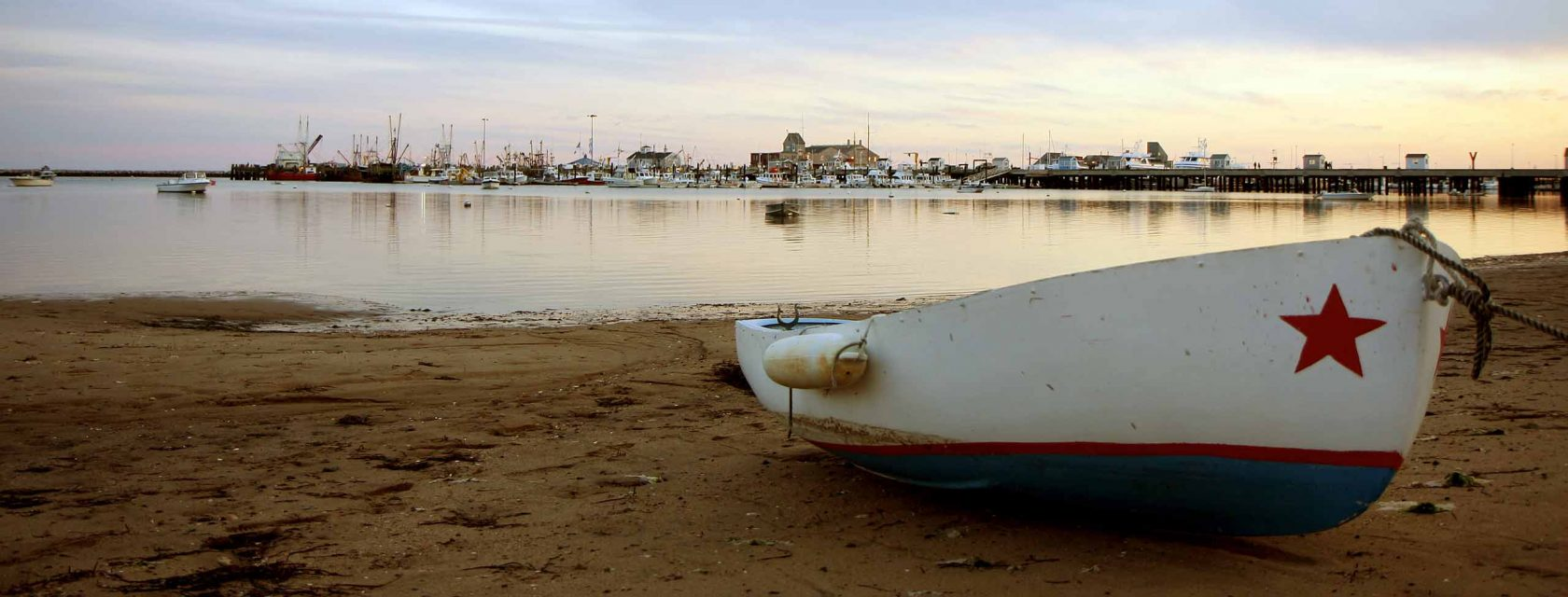 A boat with a star painted on rests on the beach in Provincetown